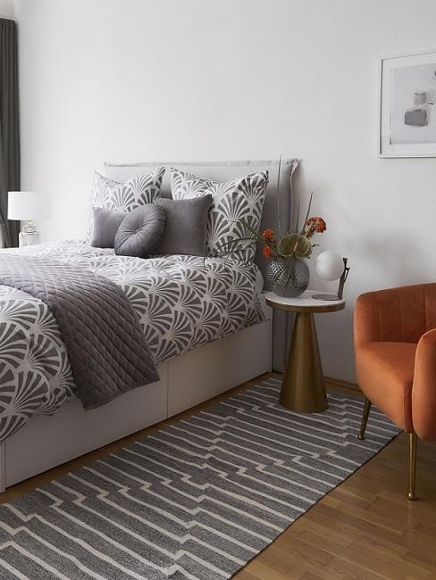 Industrial Schlafzimmer mit grauer Bettwäsche, Teppich, orangenem Sessel und goldenem Nachttisch