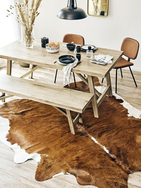 Rustikales Esszimmer im Industrial Design mit Holztisch und-bank, Kuhfellteppich und Lederstühlen