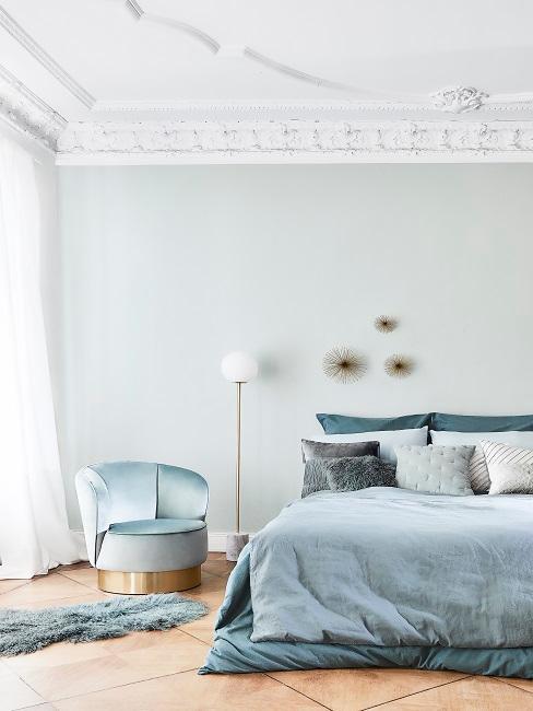 Helles Türkis an Schlafzimmerwänden mit blauem Bett und Bettwäsche, hellblauem Sessel und Lammfell