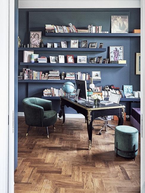 Wandfarbe Petrol im Büro mit schwarzem Tisch, Bücherregal und Samtsesseln