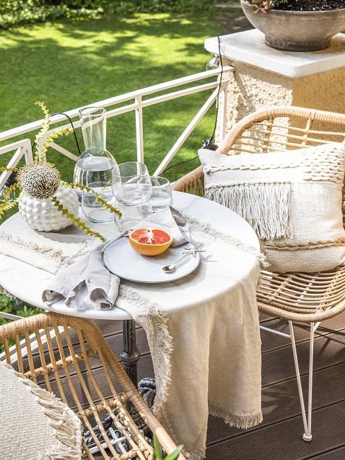 Stühle mit Kissen und gedeckter Tisch auf kleinem Balkon