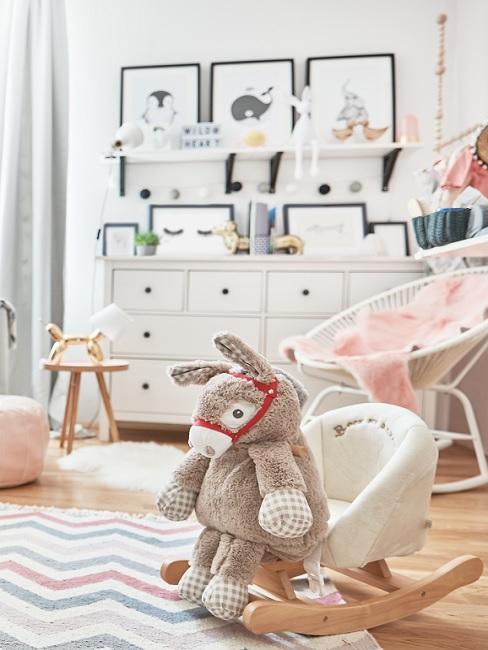 Kinderzimmer dekorieren für Mädchen mit Schaukelpferd, Bildern, rosa Decke und weißer Teppich