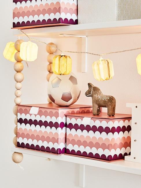 Rosafarbene Boxen im Regal als Aufbewahrung im Kinderzimmer