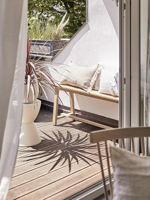 Schöner Balkon im Japandi Stil mit Holzbank, Leinenkissen und Pflanze