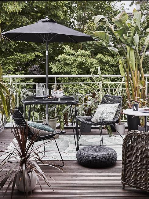 Balkon im Tropcial Style mit schwarzen Möbeln, Sonnenschrim, Kissen und Teppich mit Pflanzenmotiv