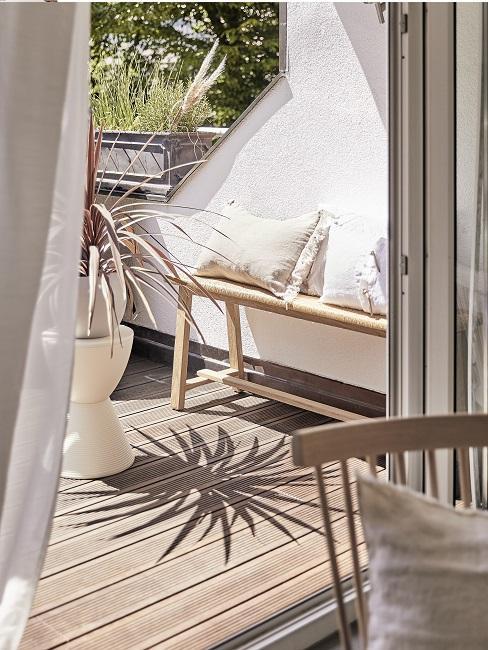 Balkon mit Holzbank, weißem Übertopf und weißen Kissen