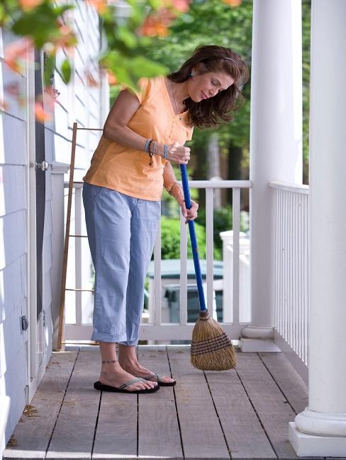 Frau reinigt Terrasse