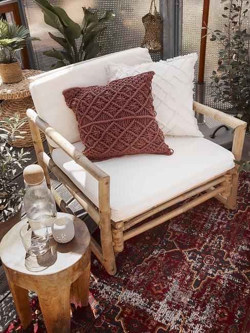 Lounge Sessel mit weißem Polster und Boho-Kissen neben Holz-Hocker
