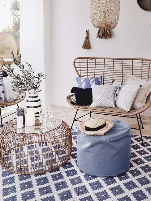 Rattan-Sofa mit Kissen auf blauem Teppich neben Couchtisch aus Rattan