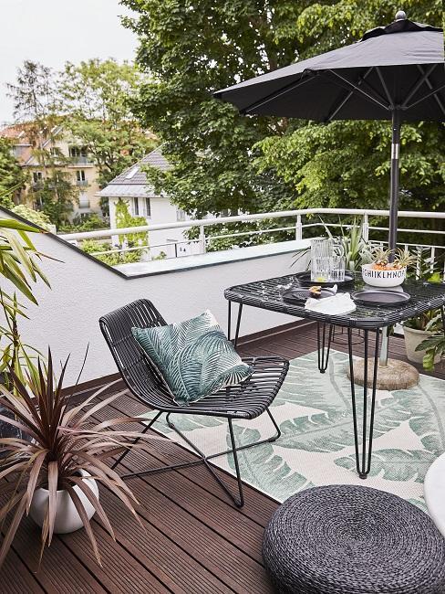Balkon mit Rattanstuhl, Tisch, Teppich und Kissen mit Pflanzenmotiv
