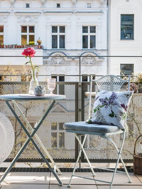 Gartenstuhl aus Metall neben Tisch auf Balkon
