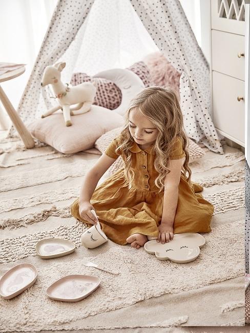 Kind spielt auf Teppich im Spielzimmer