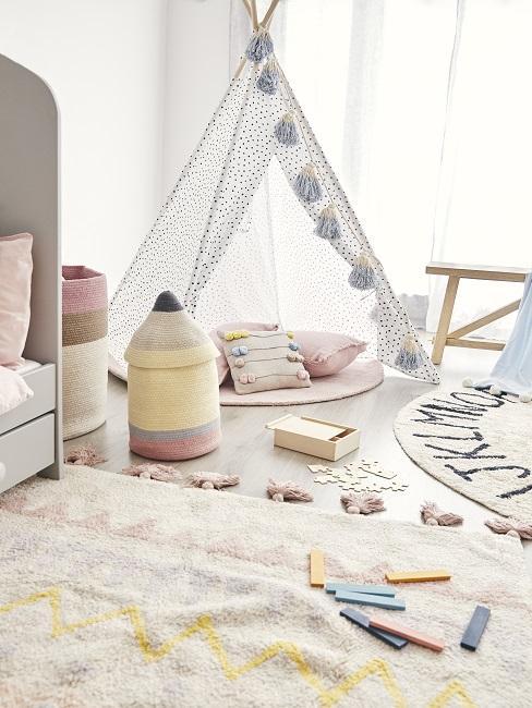 Tipi mit Kissen neben Spielteppichen und Spielzeug