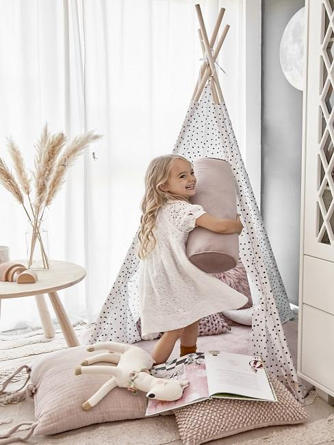 Mädchen spielt mit Kissen in Kuschelecke im Kinderzimmer