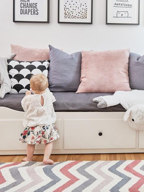 Baby steht an Bettsofa mit rosa- und lilafarbenen Kissen