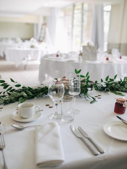 Grüne Blumengirlande auf gedecktem Tisch