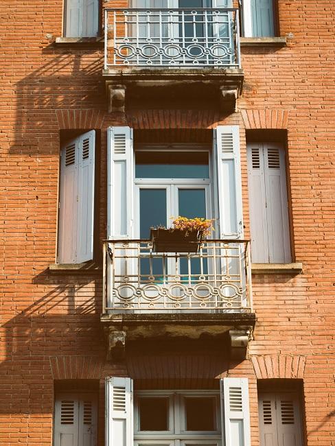 Kleiner Balkon an orangefarbener Hausfassade mit weißen Fenstern