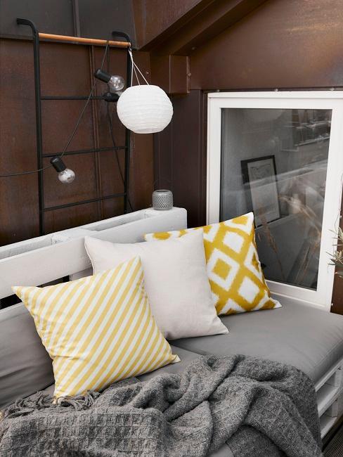Gelbe Kissen auf Palettensofa mit Decke