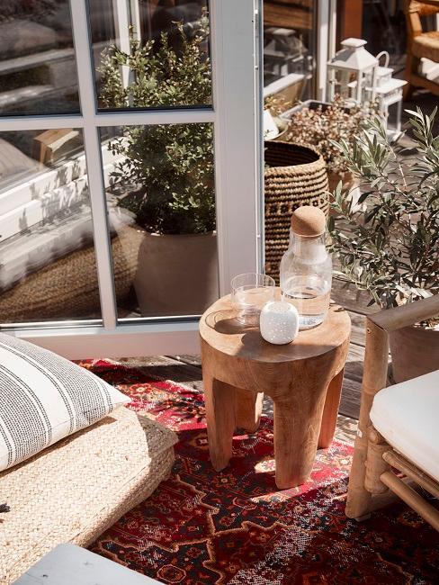Kleiner Beistelltisch aus Teakholz steht auf einer Terrasse