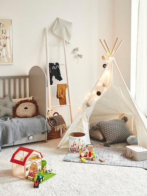 Tipi mit Lichterkette und Kuschelkissen neben Kinderbett