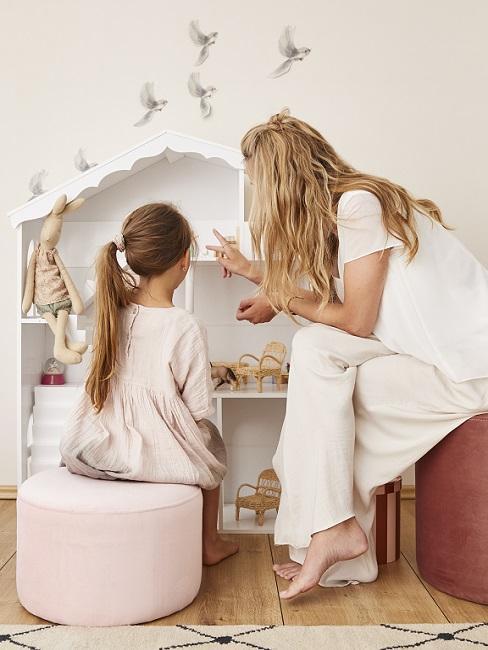 Mutter zeigt Mädchen etwas im Regal