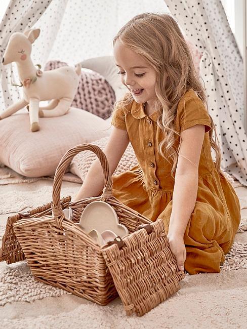 Kleines Mädchen sitzt am Boden mit Aufbewahrungskorb für den Frühjahrsputz
