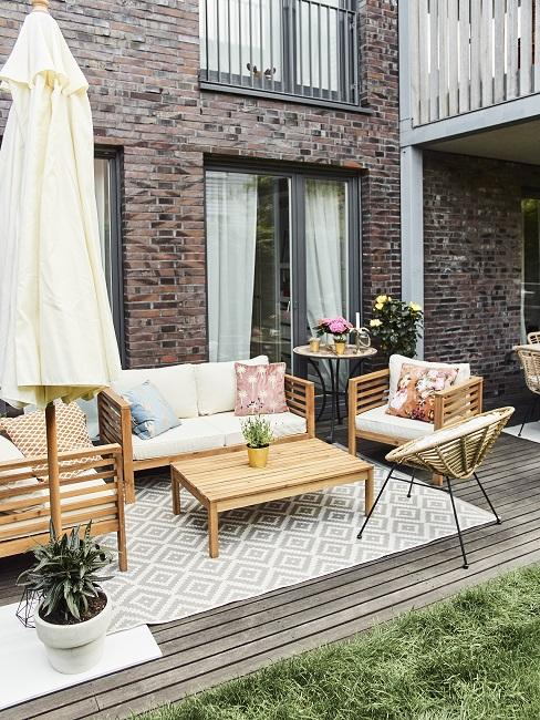 Outdoor Lougemöbel aus Holz mit Kissen und Outdoor Teppich auf Terrasse