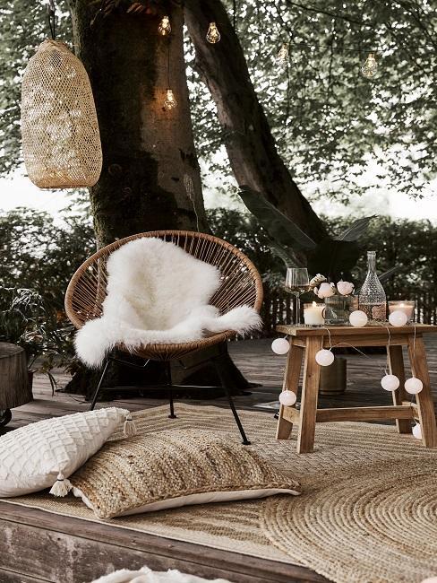 Acapulco Stuhl mit Lammfell auf Outdoor Teppich neben Hocker mit Lichterkette