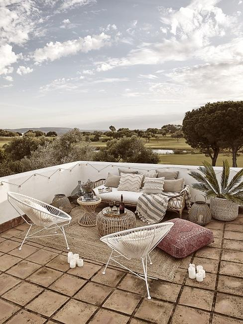Dachterrasse mit Loungesofa mit vielen Kissen in Beige, Acapulco Chairs, Bodenkissen und Beistelltischen aus Rattan