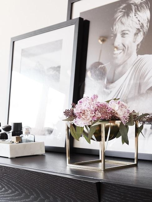 Goldene Schale mit Blumenarrangement aus rosa Pfingstrosen auf Konsole