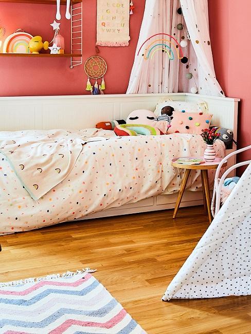 Kinderzimmer mit roten Wänden, weißen Möbeln und gepunkteter Bettwäsche