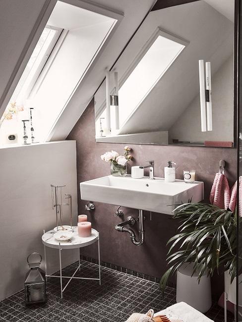 Gäste WC mit rosafarbener Wand, schwarzen Bodenfliese, rosa Deko und Zimmerpflanze
