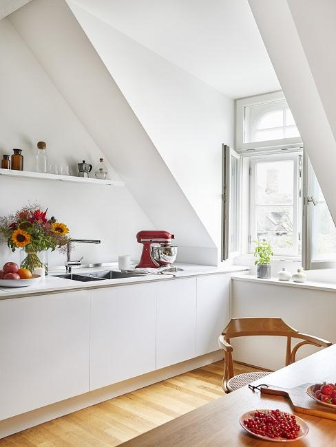Weiße Küche mit Blumen, roter Küchenmaschine und Esstisch
