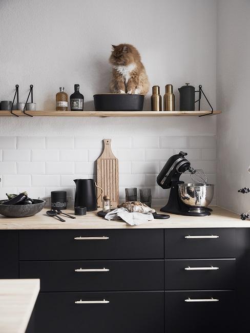 Schwarze Küchezeile mit Holzplatte und goldenen Griffen