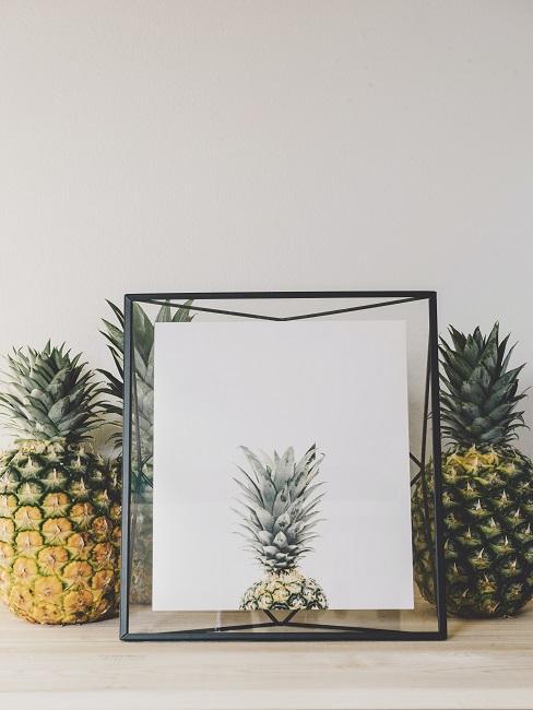 Ananas-Bild in schwarzem Bilderrahmen neben zwei Ananas