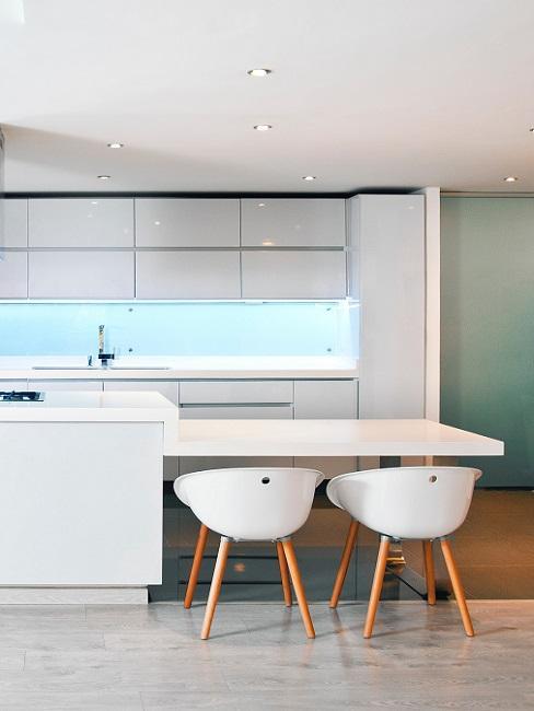Weiße Küche mit einem Tresen als Essplatz und zwei Stühlen