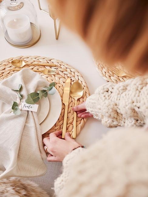 Frau die Besteck zu einem Teller mit Serviette legt