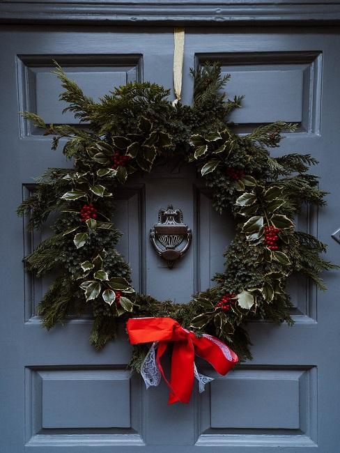 Kranz mit roter Schleife an einer blauen Tür