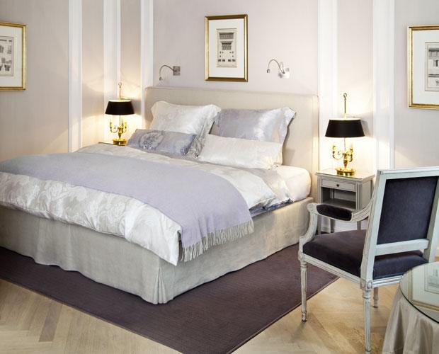 Schlafzimmer mit gemachtem Bett in Weiß und Grau