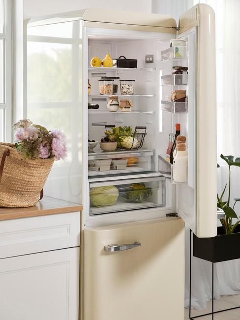 Geöffneter Kühlschrank mit Lebensmitteln in beige