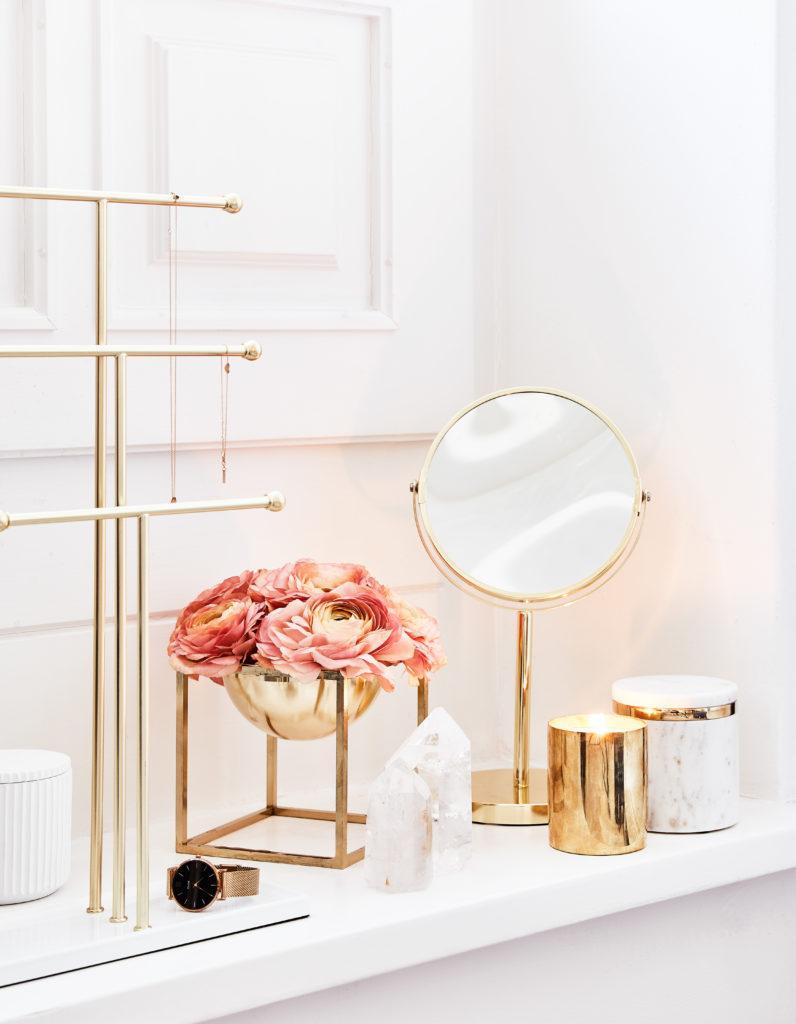 Kleiner goldener Kosmetikspiegel steht glänzendauf einer weißen Kommode