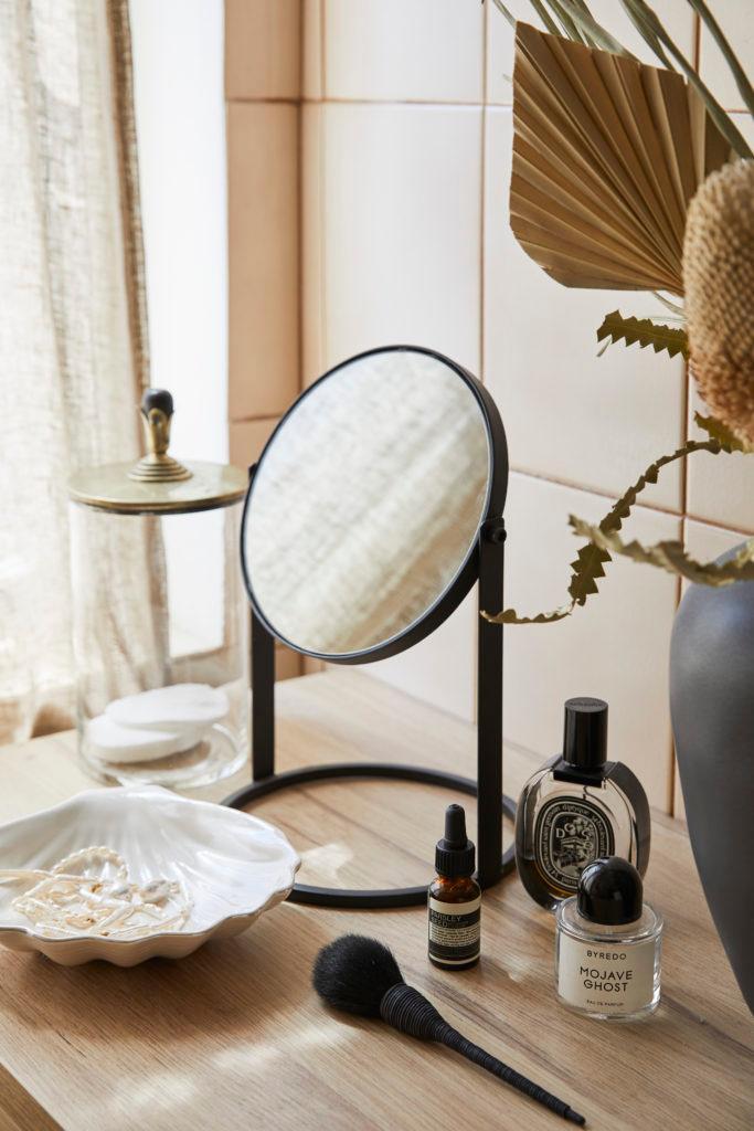 Kleiner schwarzer Kosmetikspiegel steht auf Kommode aus Holz