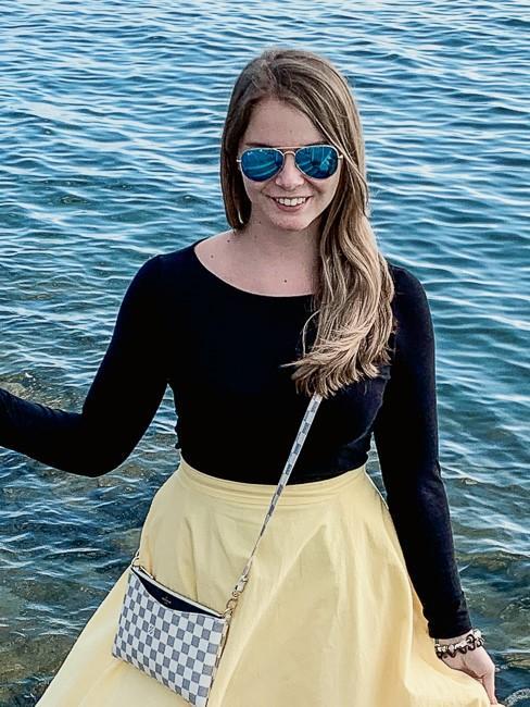Frau vor Meereswasser mit Sonnenbrille