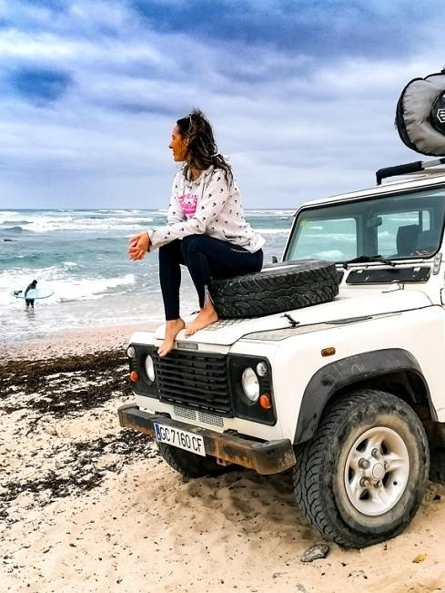 Frau auf dem Auto sitzend am Strand