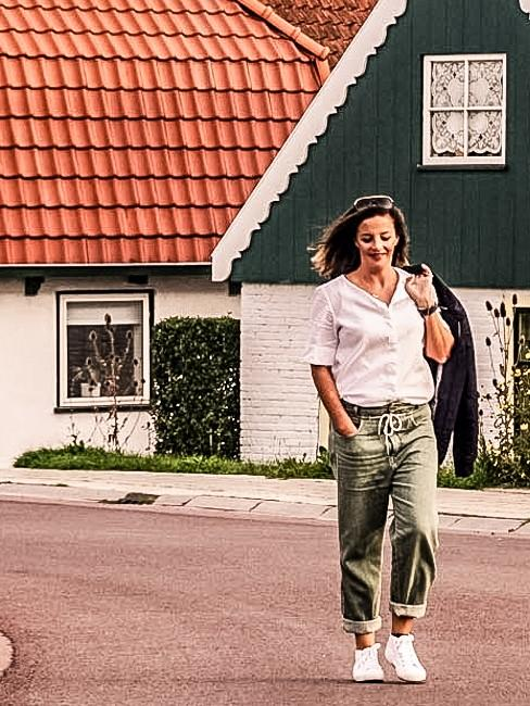 Frau auf Straße gehend vor Häusern