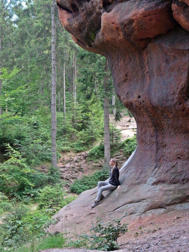 Frau an einem Berg im Wald sitzend