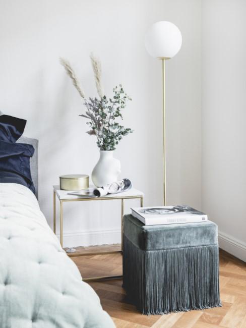 Sitzwürfel aus Samt mit Fransenoptik steht im Schlafzimmer