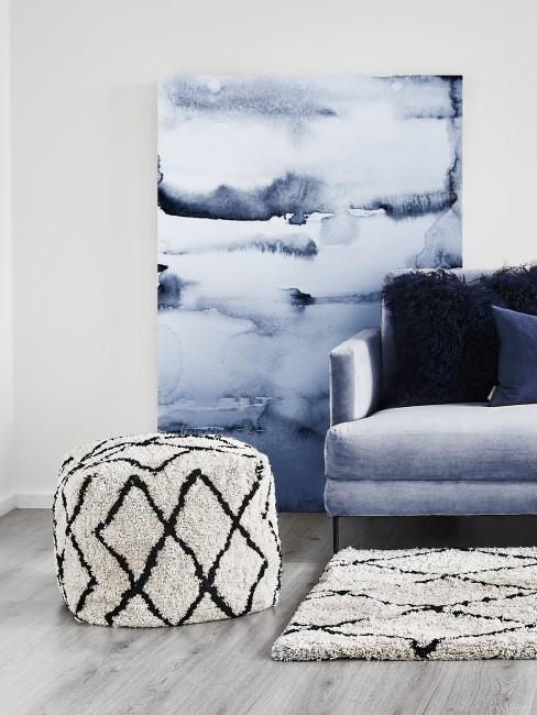 Sitzwürfel steht im Wohnzimmer vor blauem Gemälde