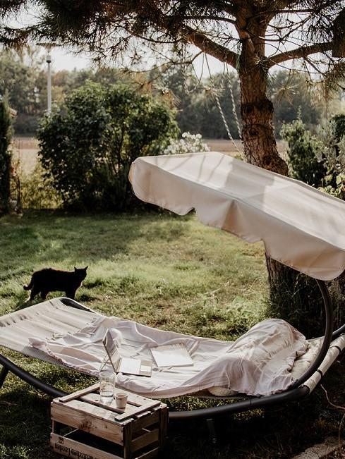 Sonnenliege im Garten mit schwarzer Katze