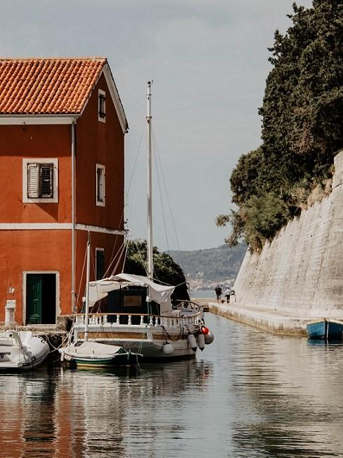 Schiff vor rotem Haus